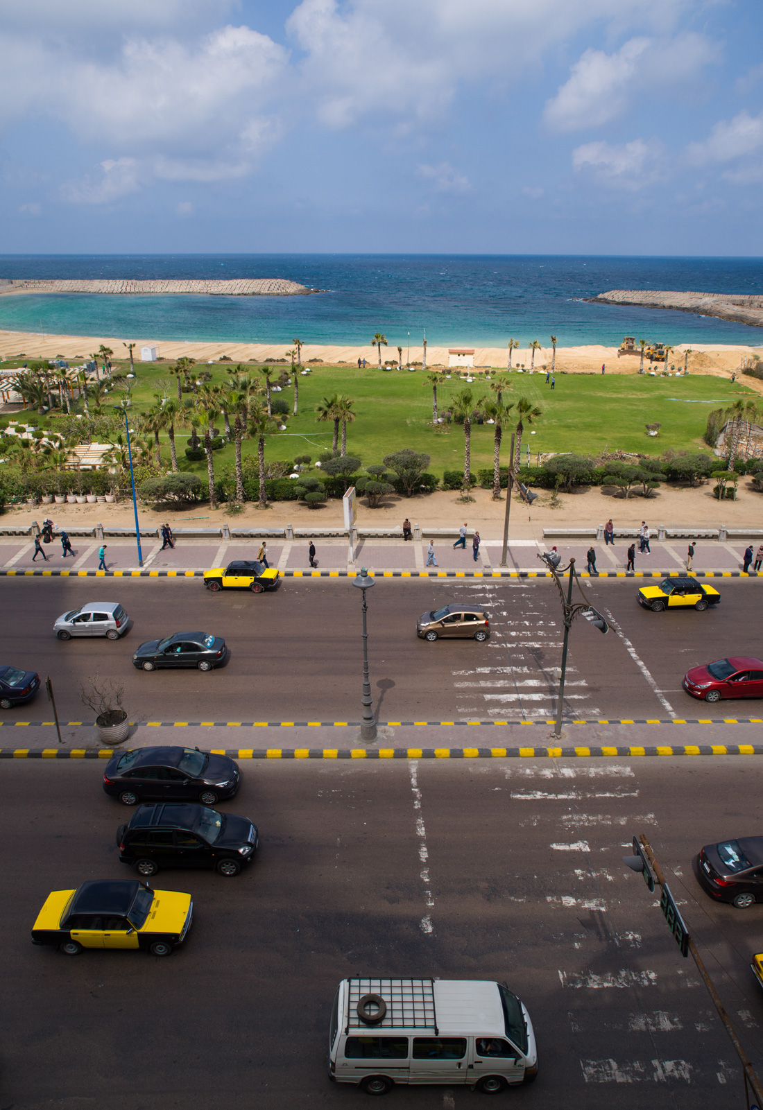 A view from an upscale hotel, across the corniche road to the private beach and the sea beyond.