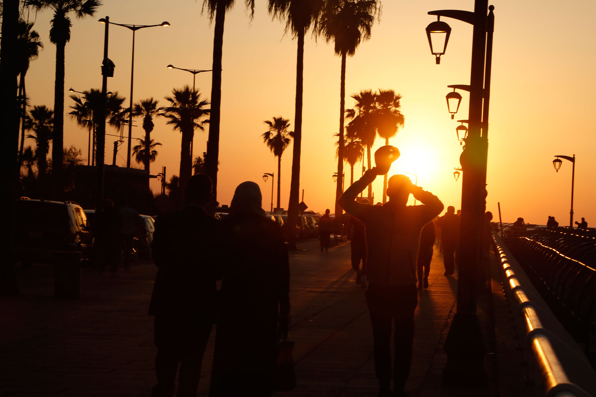 People walk along the corniche at sunset.