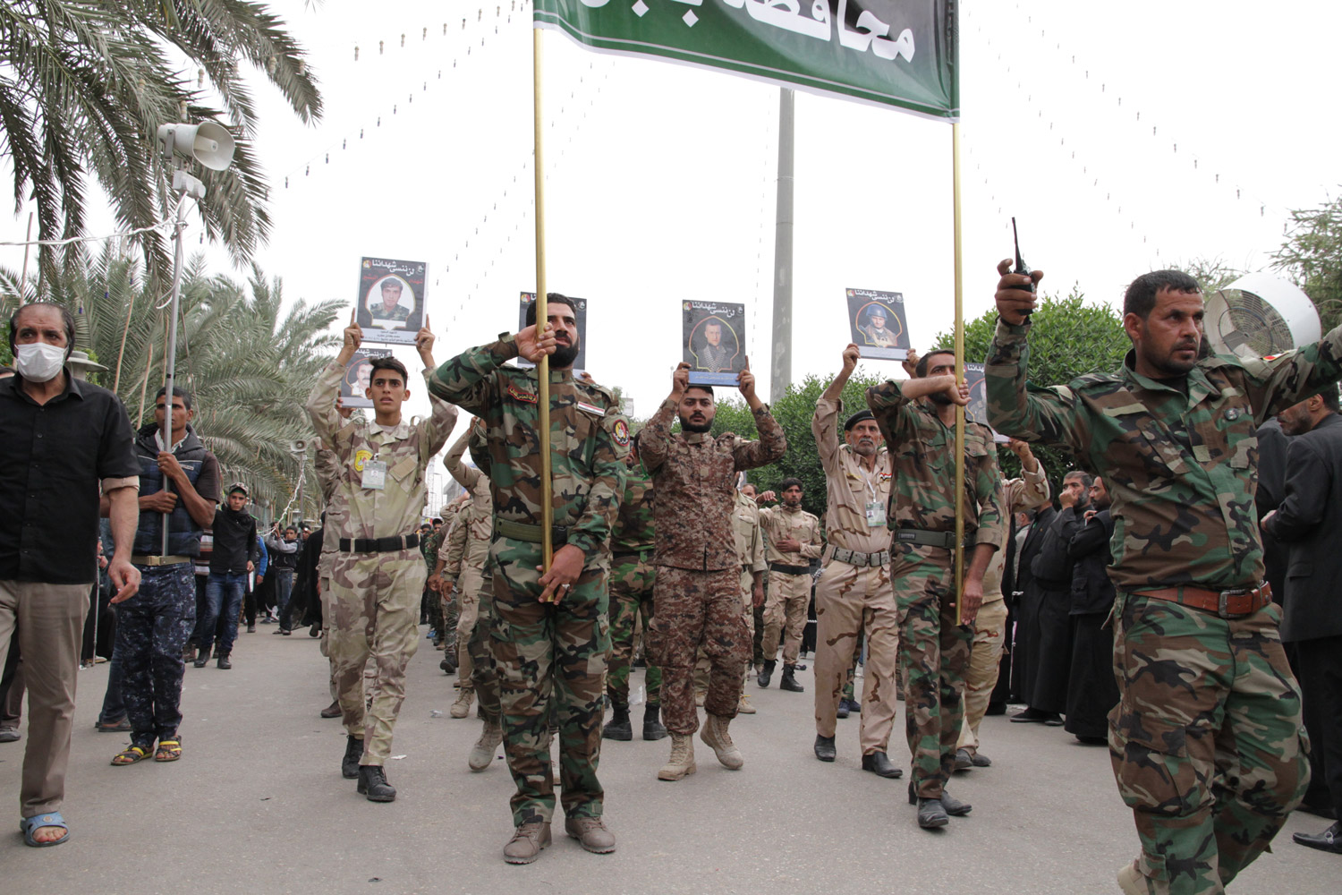 Members of the PMF or Hashd al-Shaabi depicting their martyrs during a march in Iraq, November 2016.